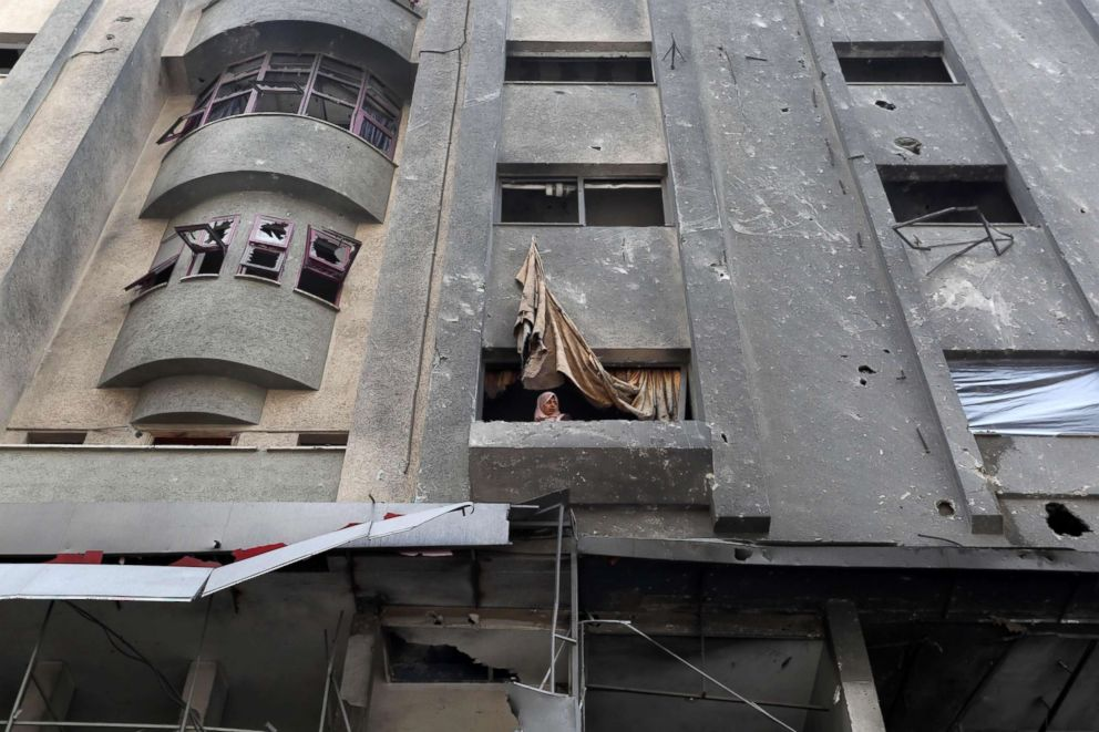 PHOTO: A Palestinian woman looks out of the window after Israeli air strikes destroyed buildings in Gaza City, Nov. 14, 2018.