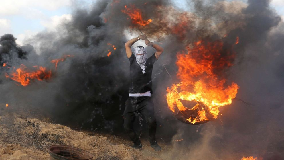 Palestinian protesters burn tires in response to Israeli forces' intervention on the 14th week of right of return march along the border with Israel, east of Khan Yunis in the southern Gaza Strip on June 29, 2018.