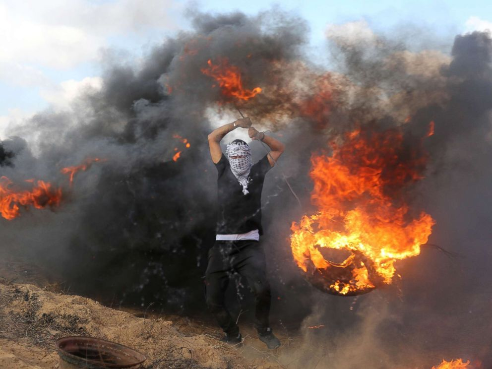 PHOTO: Palestinian protesters burn tires in response to Israeli forces intervention on the 14th week of right of return march along the border with Israel, east of Khan Yunis in the southern Gaza Strip on June 29, 2018.
