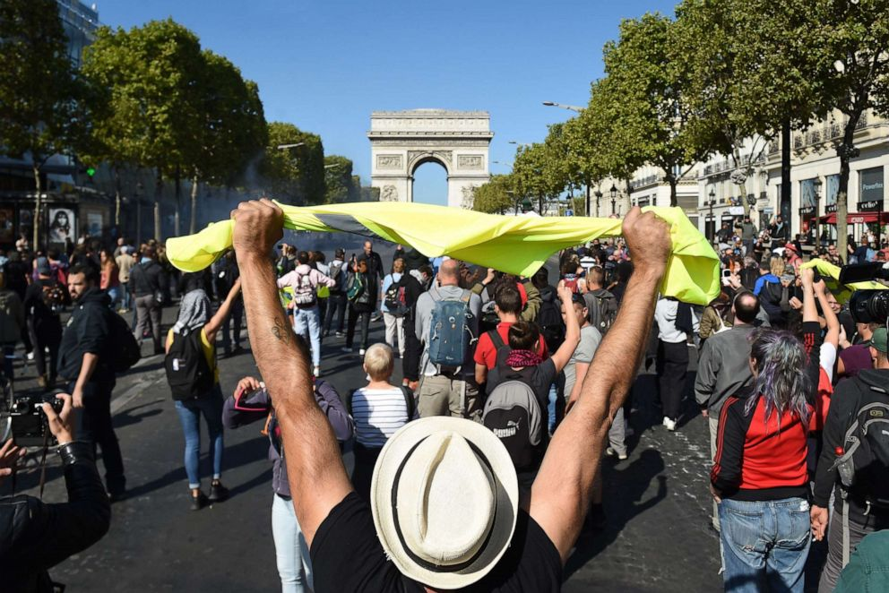 PHOTO: A man holds up a yellow vest in front of the Arc de Triomphe on the Champs Elysees avenue during an anti-government demonstration called by the yellow vest (gilets jaunes) movement, on September 21, 2019 in Paris.
