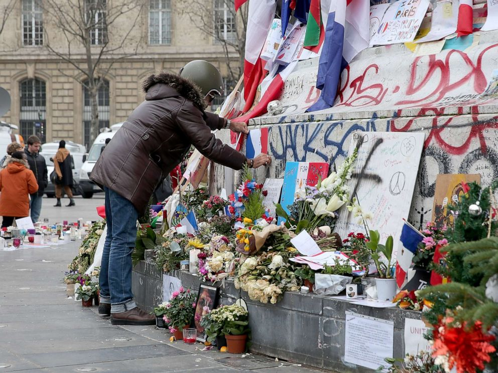 PHOTO: A man is seen posting a French flag on the monument of the Place de la Republique where people continue to pay tribute to the Paris Attacks victims one month after they occurred, Dec. 13, 2015, in Paris.
