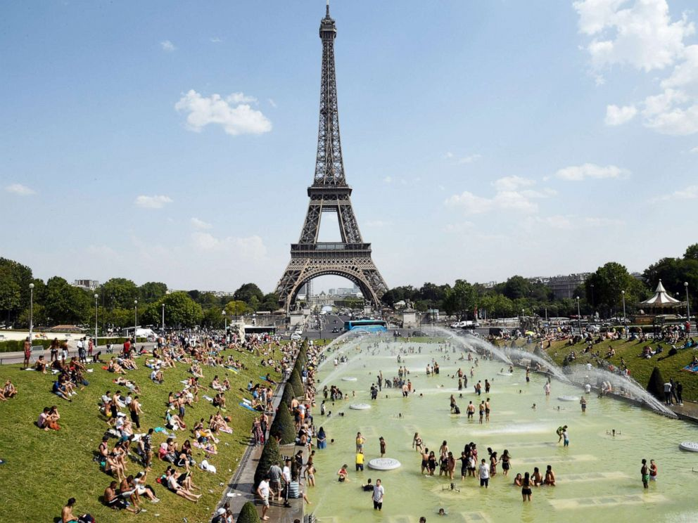 PHOTO:People cool off and sunbathe by the Trocadero Fountains next to the Eiffel Tower in Paris, on July 25, 2019 as a new heatwave hits the French capital.