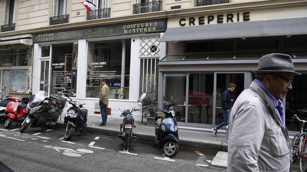 People walk on Monsigny street in Paris, May 13, 2018, on the site where a man attacked several people with a knife the night before.