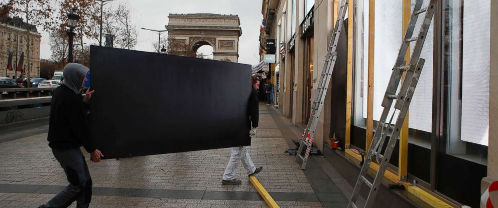 PHOTO: Workers carry a wooden piece to protect shop windows on the Champs-Elysees avenue, Friday, Dec. 7, 2018 in Paris.