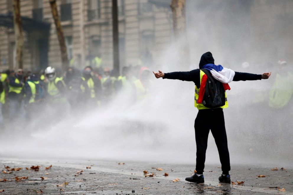 PHOTO: Protesters wearing yellow vests, a symbol of a French drivers protest against higher diesel taxes, face off with riot police during clashes at the Place de lEtoile in Paris, Dec. 1, 2018.