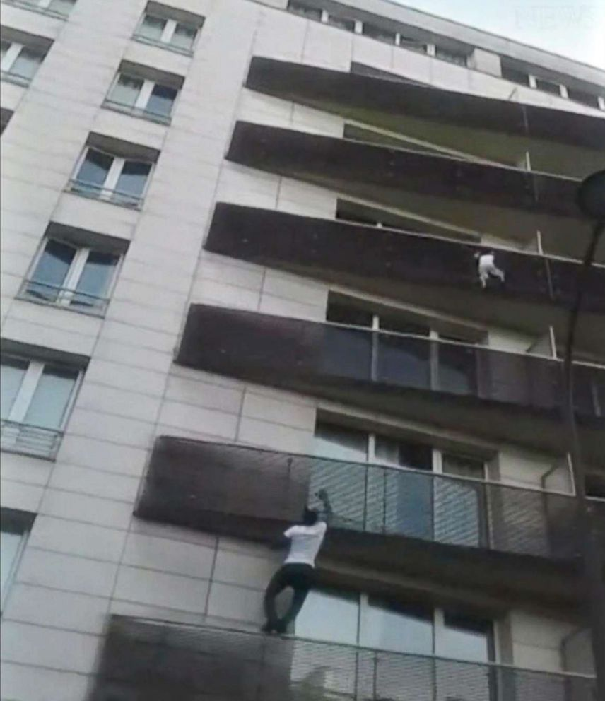 PHOTO: A video by Tadek Dandach shows Mamoudou Gassama, 22, from Mali, scaling the outside of an apartment building to rescue a four-year-old boy in Paris.  Father of boy dangling from Paris balcony was out playing Pokémon Go, prosecutor says Father of boy dangling from Paris balcony was out playing Pokémon Go, prosecutor says paris rescue 01 rc 180528 hpEmbed 13x15 992