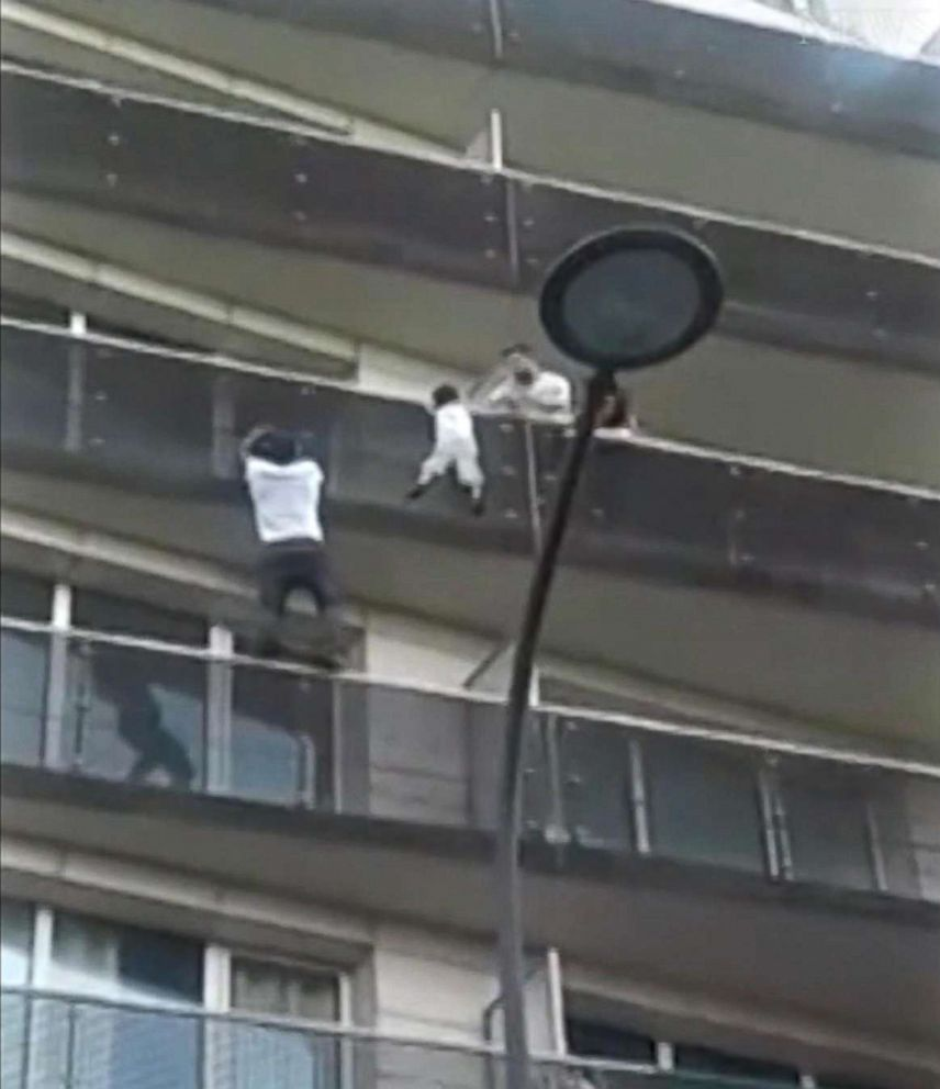 PHOTO: A video by Tadek Dandach shows Mamoudou Gassama, 22, from Mali, scaling the outside of an apartment building to rescue a four-year-old boy in Paris.  Father of boy dangling from Paris balcony was out playing Pokémon Go, prosecutor says Father of boy dangling from Paris balcony was out playing Pokémon Go, prosecutor says paris rescue 03 rc 180528 hpEmbed 13x15 992