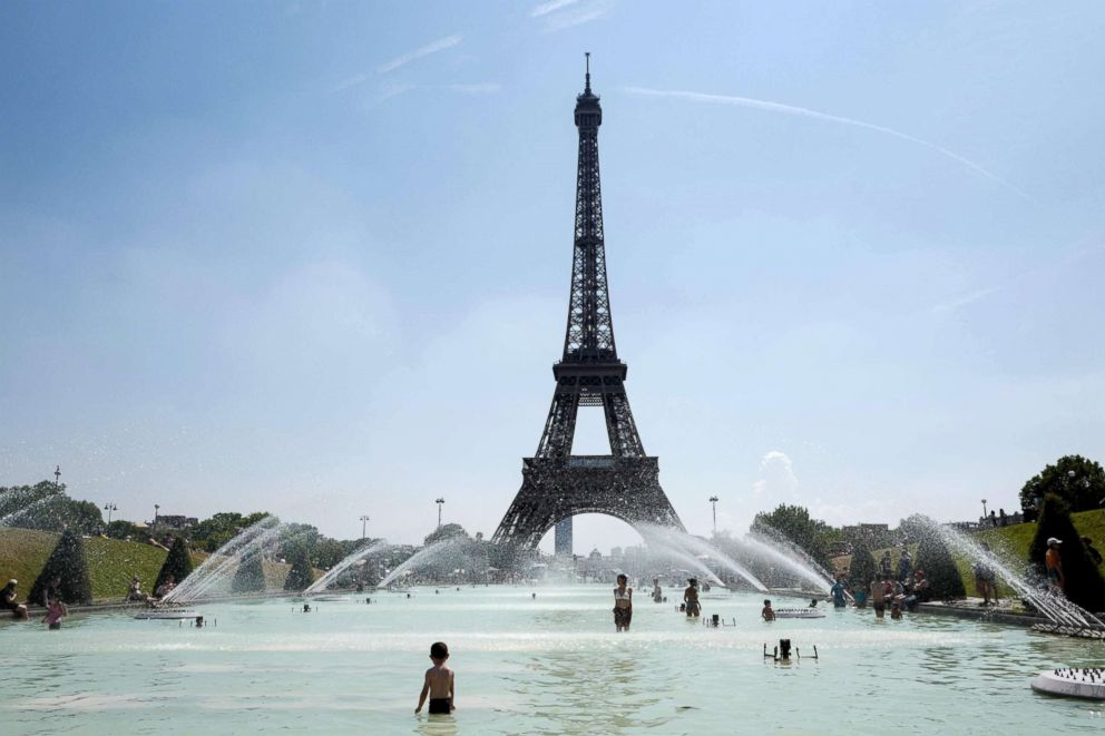 People cool themselves at the Trocadero Fountain in front of the Eiffel Tower in Paris, July 27, 2018, as a heatwave continues across northern Europe.