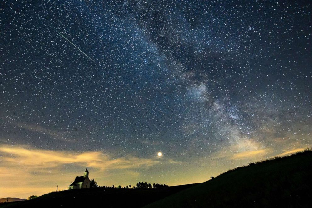 PHOTO: A meteor streaks through the sky past planet Mars and Milky Way during the Perseid meteor shower above the village of Gemersky Jablonec in Slovakia, Aug. 13, 2018.