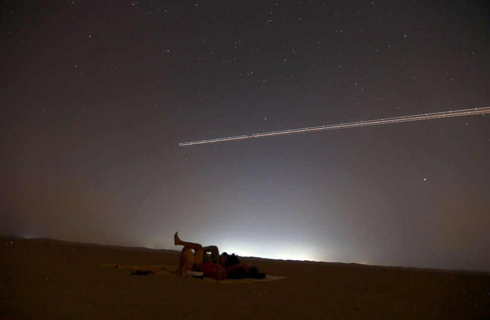 PHOTO: People lie on the ground to watch the Perseid meteor shower as an airplane flies over the Al Qudra desert, in Dubai, United Arab Emirates, Aug. 12, 2018.