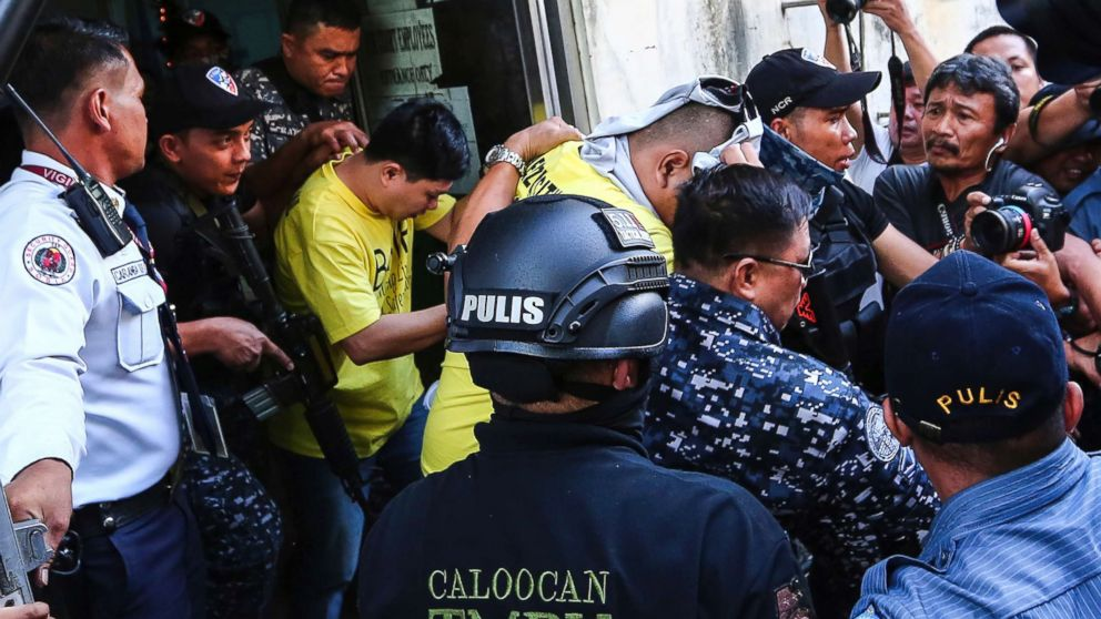Two of three police officers are escorted out of the courtroom after being found guilty and sentenced up to 40 years without parole for the killing of a student, Nov. 29, 2018, in Caloocan city, Philippines.