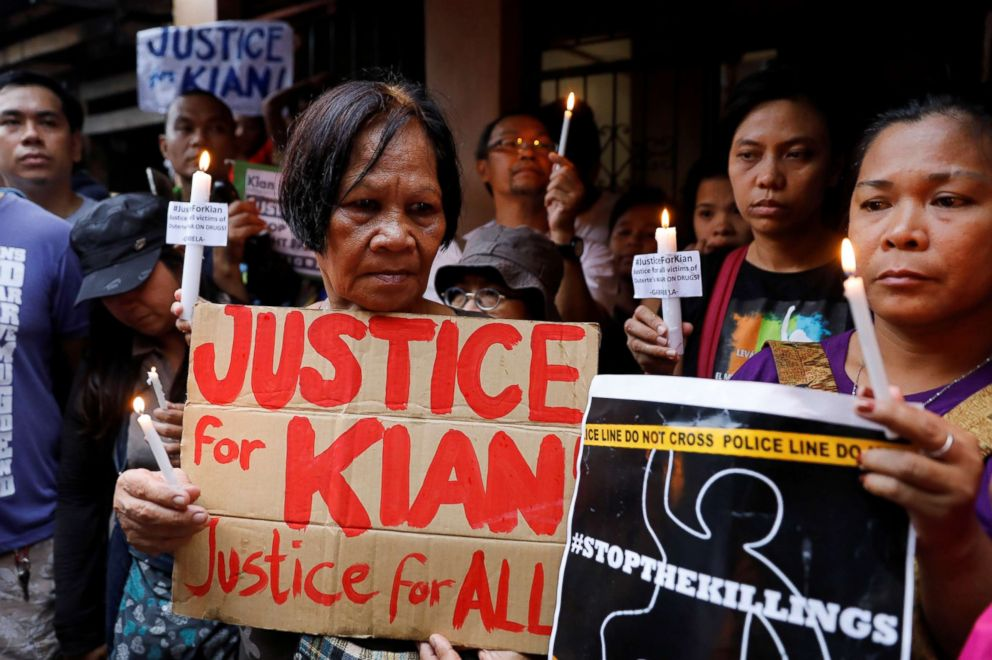 Protesters hold placards and lit candles at the wake of Kian Loyd delos Santos, a 17-year-old high school student, who was among the people shot dead in President Rodrigo Duterte's war on drugs, in Caloocan city, Philippines, Aug. 21, 2017.