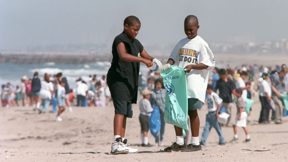 In this file photo, Terrell McNeal, ll, and Tareall Atkins, 10, from Westminister Elementary School in Venice, Calif., clean up plastic bottles on the beach at Dockweiler State beach, April 22, 1997.