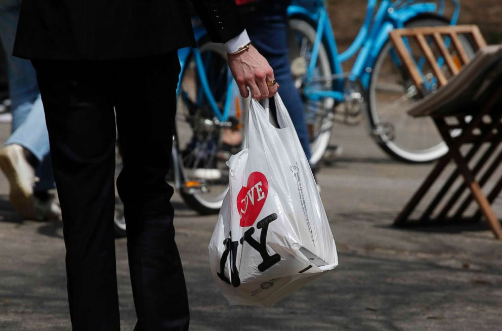 PHOTO: A man holds a plastic shopping bag as he visits Central Park on April 26, 2018 in New York. In April New York Gov. Andrew Cuomo called for a ban on plastic carryout bags at stores statewide.