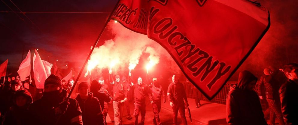 PHOTO: Polish nationalists carry a flag Death to the enemies of Homeland and light flares as they take part in the March of Independence 2017 in Warsaw, Poland, Nov. 11, 2017.