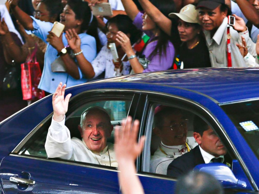 PHOTO: Pope Francis waves as as he is welcomed by the crowd along a road in Yangon, Myanmar, Nov. 27, 2017.