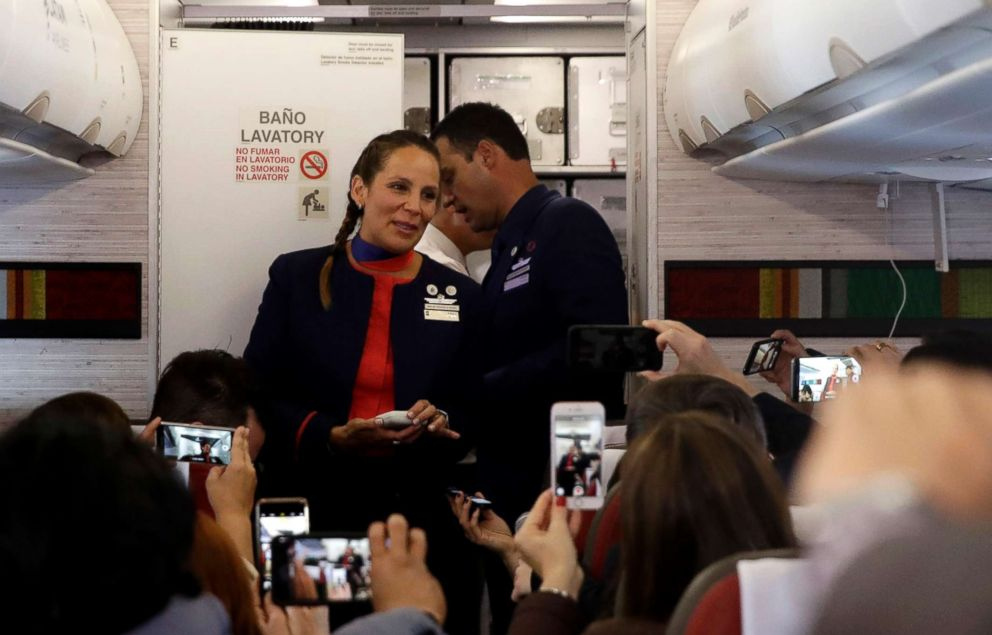 PHOTO: Flight attendants Paula Podest, front, and her husband Carlos Ciuffardi, behind, talk with journalists during a flight from Santiago to Iquique, Chile, after Pope Francis married them in-flight, Jan. 18, 2018.