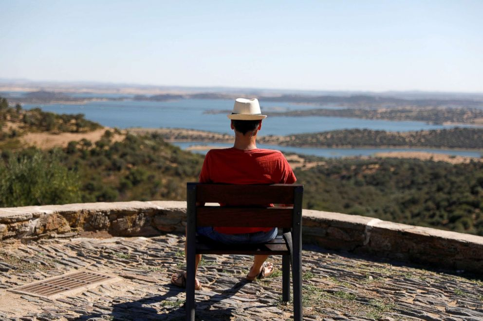 PHOTO: A man waits for the sunset at a viewpoint near Alqueva reservoir, in Monsaraz, Portugal, Aug. 8, 2018.