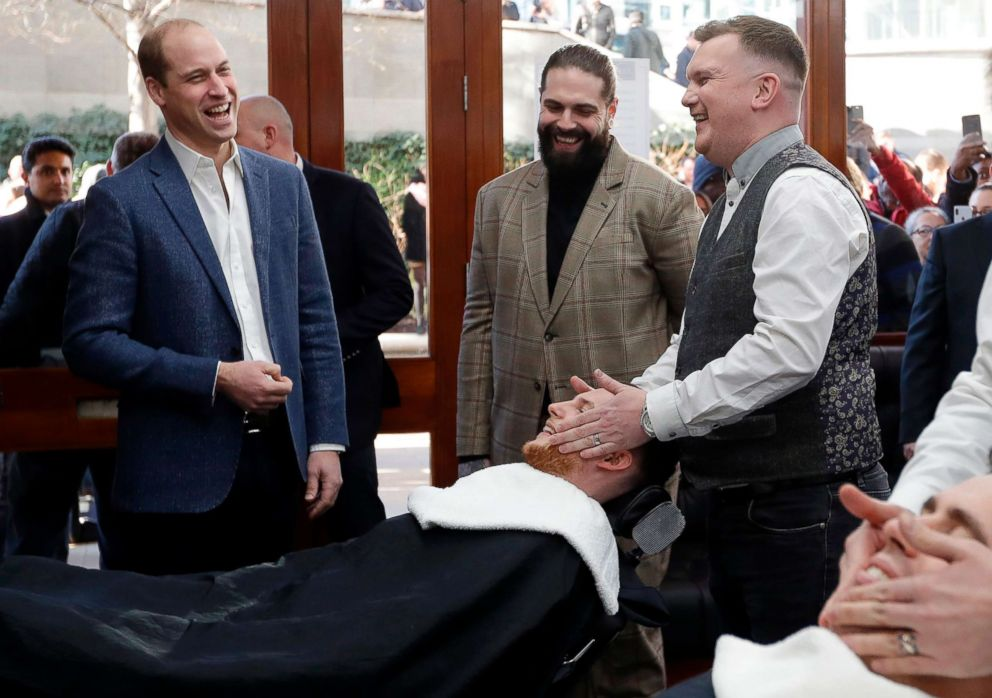 Britain's Prince William, Duke of Cambridge, speaks to Tom Chapman, founder of the charity Lions Barber Collective (C), and barber Daniel Davies (R), during a visit to Pall Mall Barbers in London, Feb. 14, 2019.