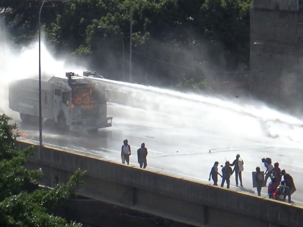 PHOTO: A police vehicle sprays anti-government protesters with a water canon in Caracas, Venezuela.