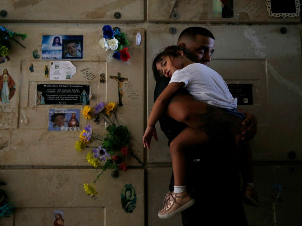 PHOTO: Orlando Gonzalez holds his daughter during the funeral of their neighbor Victor Ruiz Ramos in Corozal, Puerto Rico, Oct. 02, 2017. Ruiz died after he no longer able to power a machine that treated his emphysema.
