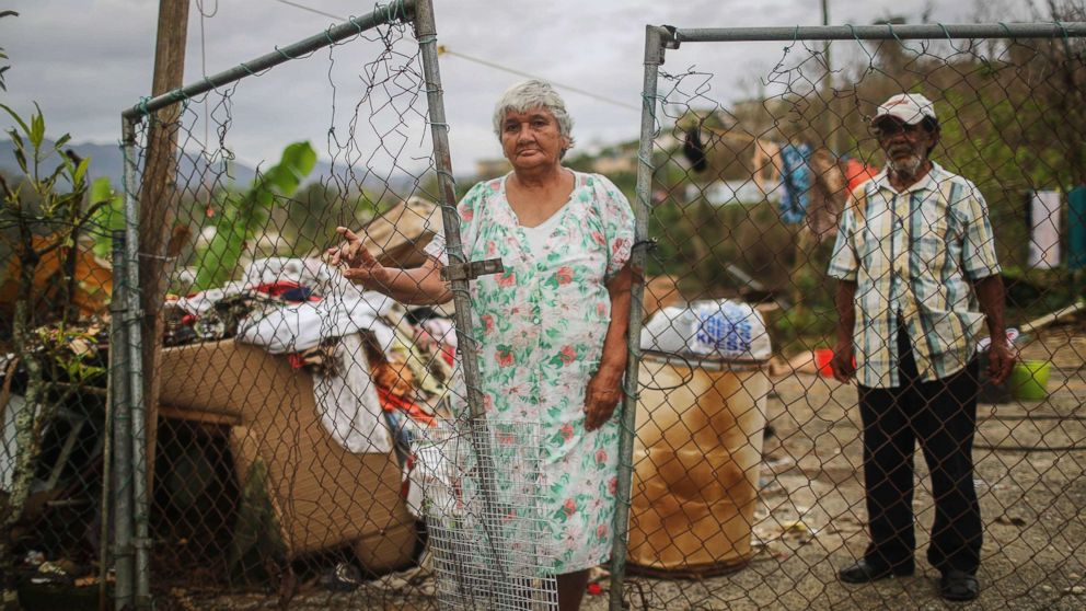 Luz Sota Rivera (C) and Francisco Nazario Aviles pose outside their damaged home, with debris removed from their home uncollected in the driveway, three weeks after Hurricane Maria hit the island, Oct. 12, 2017 in Jayuya, Puerto Rico.