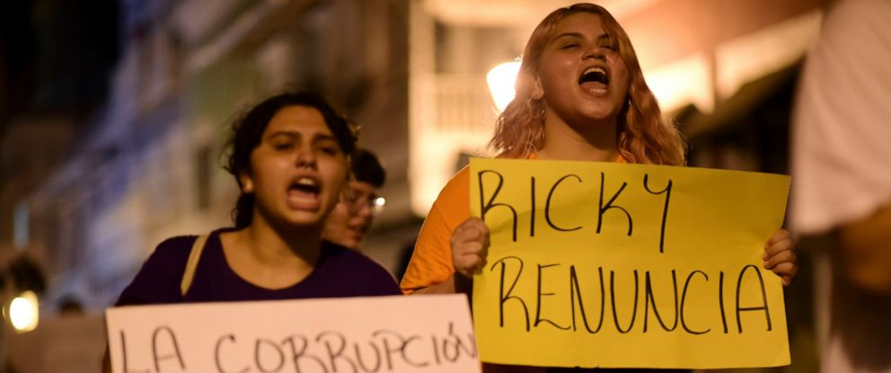 "PHOTO: Demonstrators holding signs that read in Spanish ""Corruption is violence"" and ""Ricky renounce"", protest near the executive mansion denouncing a wave of arrests for corruption that has shaken the country, demanding the resignation of the governor."