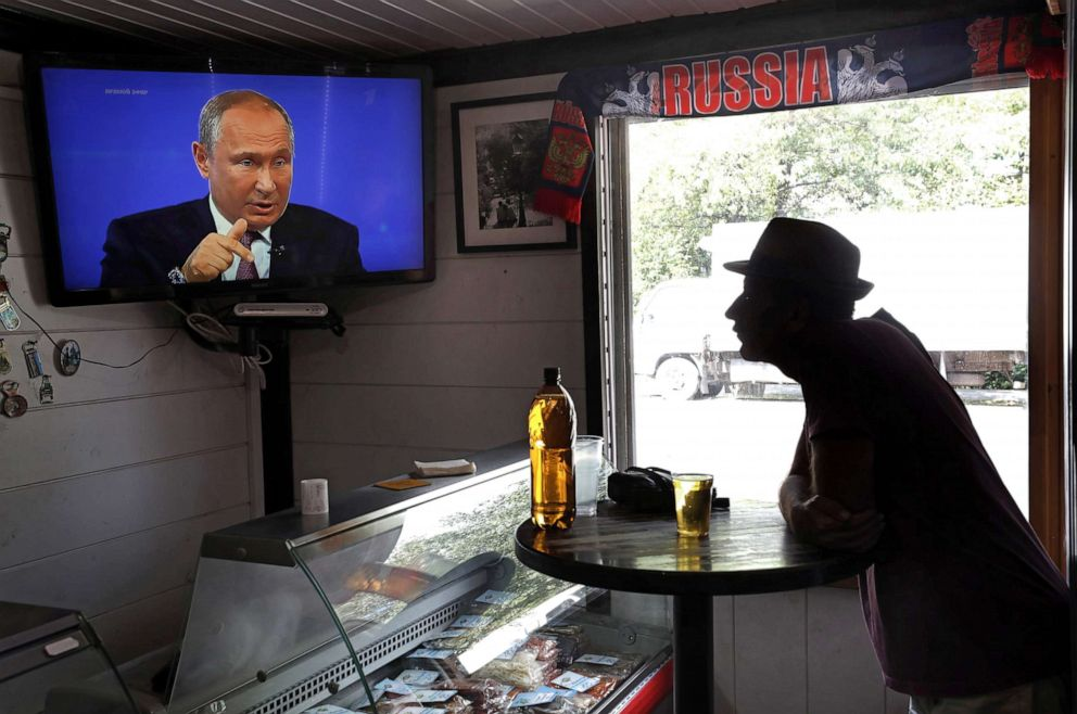 PHOTO: A bar patron watches on Russian President Vladimir Putin during a annual live broadcast call-in program outside Moscow, June 20, 2019.