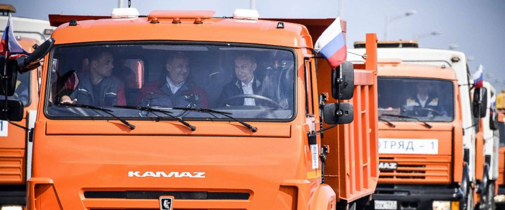 PHOTO: Russian President Vladimir Putin drives a construction truck across the new 12 mile road-and-rail Crimean Bridge over the Kerch Strait linking mainland Russia to Moscow-annexed Crimea during the opening ceremony, May 15, 2018.