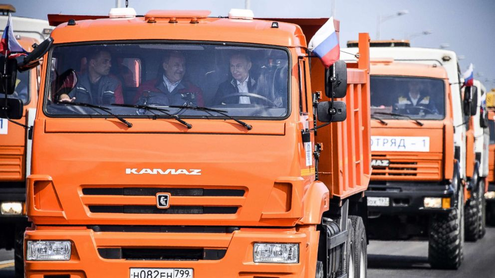 Russian President Vladimir Putin drives a construction truck across the new 12 mile road-and-rail Crimean Bridge over the Kerch Strait linking mainland Russia to Moscow-annexed Crimea during the opening ceremony, May 15, 2018.