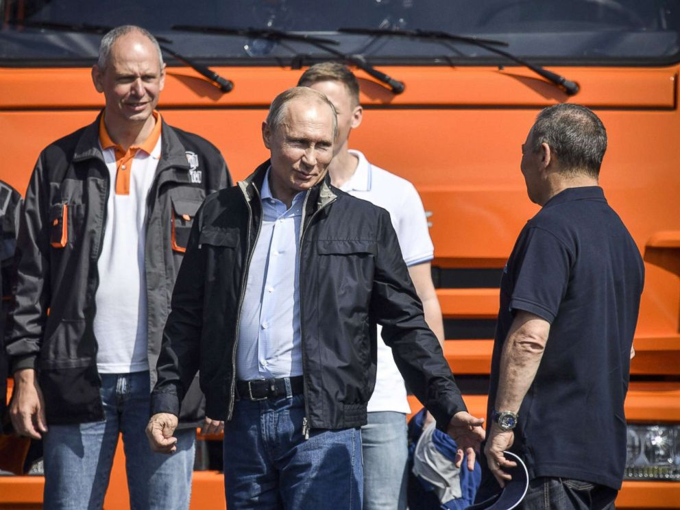 PHOTO: Russian President Vladimir Putin (C) talks to workers after driving a construction truck across the new 12 miles road-and-rail Crimean Bridge over the Kerch Strait that links mainland Russia to Moscow-annexed Crimea, May 15, 2018.