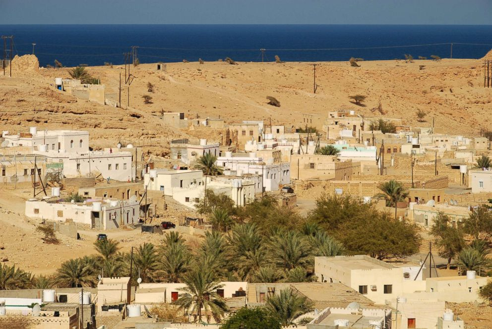 PHOTO: An elevated view of small houses and trees in an arid area of Qalhat, Oman.