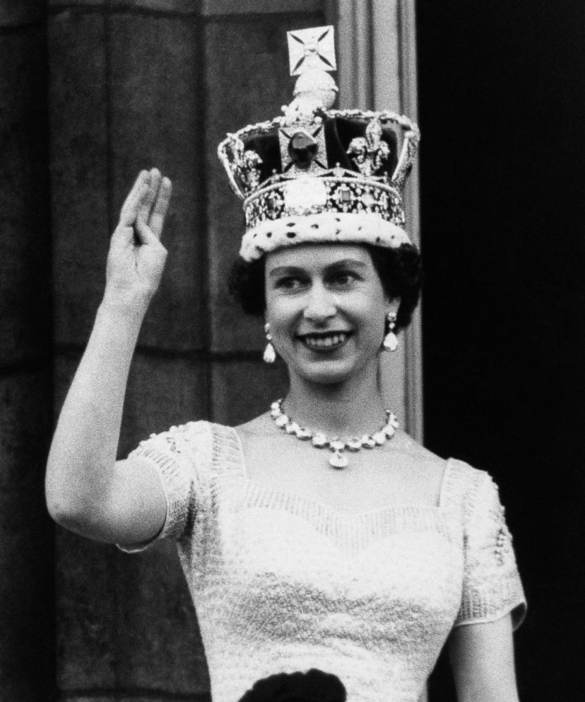PHOTO: Queen Elizabeth II, wearing the Imperial Crown, smiles and waves to a crowd from balcony of Buckingham Palace on June 3, 1953, in London, on returning from Westminster Abbey following her coronation.