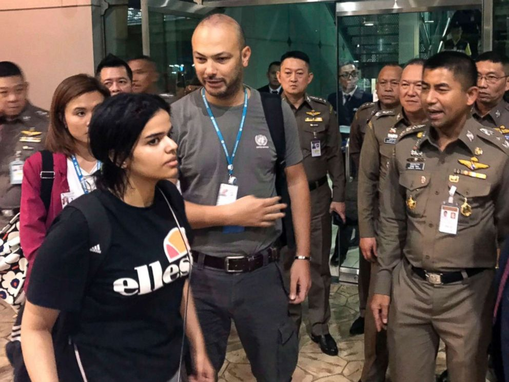 Immigration Bureau Saudi woman Rahaf Mohammed Alqunun foreground walks by Chief of Immigration Police Maj. Gen. Surachate Hakparn right before leaving the Suvarnabhumi Airport in Bangkok