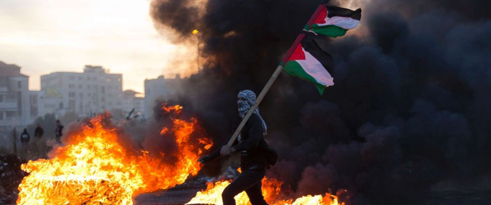 PHOTO: A Palestinian protester flies Palestinian flags during clashes with Israeli troops following protests against President Donald Trumps decision to recognize Jerusalem as the capital of Israel, in the West Bank city of Ramallah, Dec. 9, 2017.