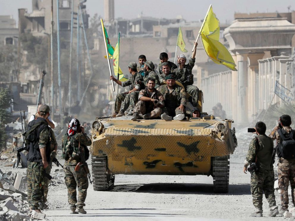 PHOTO: Fighters of Syrian Democratic Forces ride atop of an armoured vehicle after Raqqa was liberated from the Islamic State militants, in Raqqa, Syria, Oct. 17, 2017.