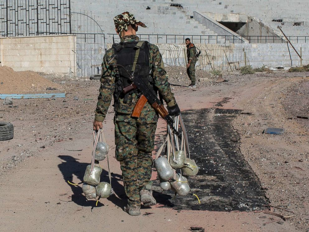 PHOTO: A member of the Syrian Democratic Forces carries bombs they use to destroy IEDs as they clear the stadium where it was the last stand for Islamic State fighters before most fighters handed in and left Raqqa, Syria on Oct. 18, 2017.