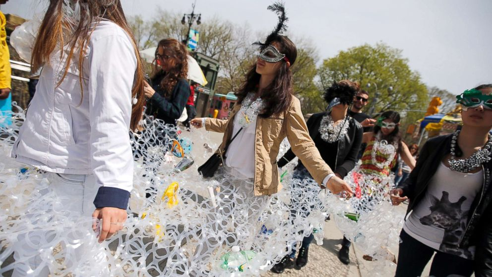 """Demonstrators march together in plastic six pack rings during a demonstration to mark Earth Day in Manhattan, April 22, 2014, in this file photo in New York City. Members of the Oragami Project, a movement that encourages environmental responsibility by transforming plastic six pack rings into wearable art, demonstrated """"trapped"""" in the plastic six pack rings to symbolize birds and and other wildlife caught in trash."""