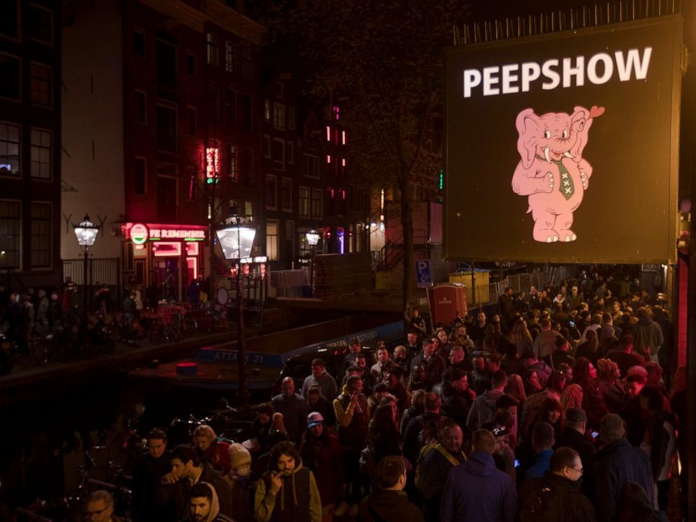 PHOTO: Tourists are bathed in a red glow emanating from the windows and peep shows neon lights are packed shoulder to shoulder as they shuffled through the alleys in Amsterdams red light district, Netherlands, Friday evening, March 29, 2019.