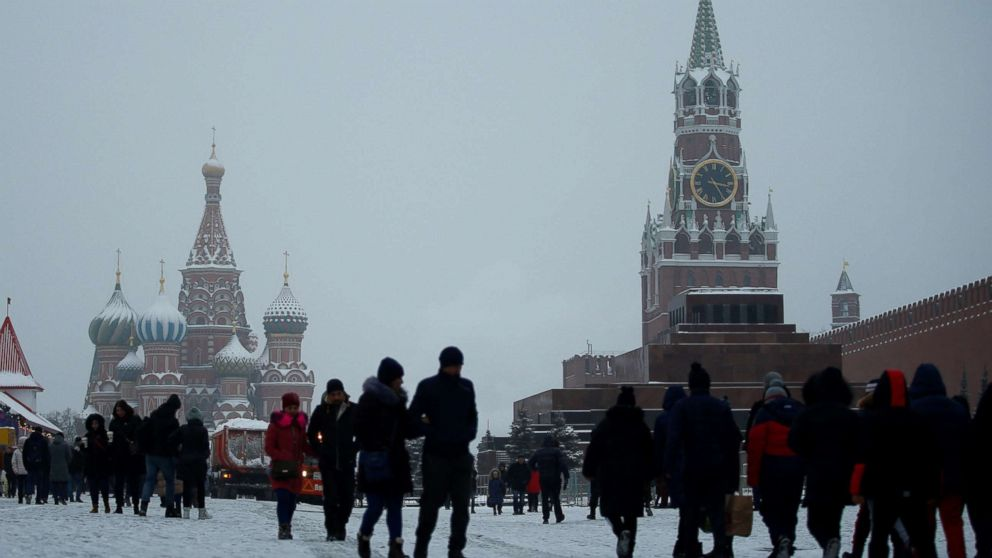People walk during snowfall in Red Square in Moscow, Dec. 24, 2018.