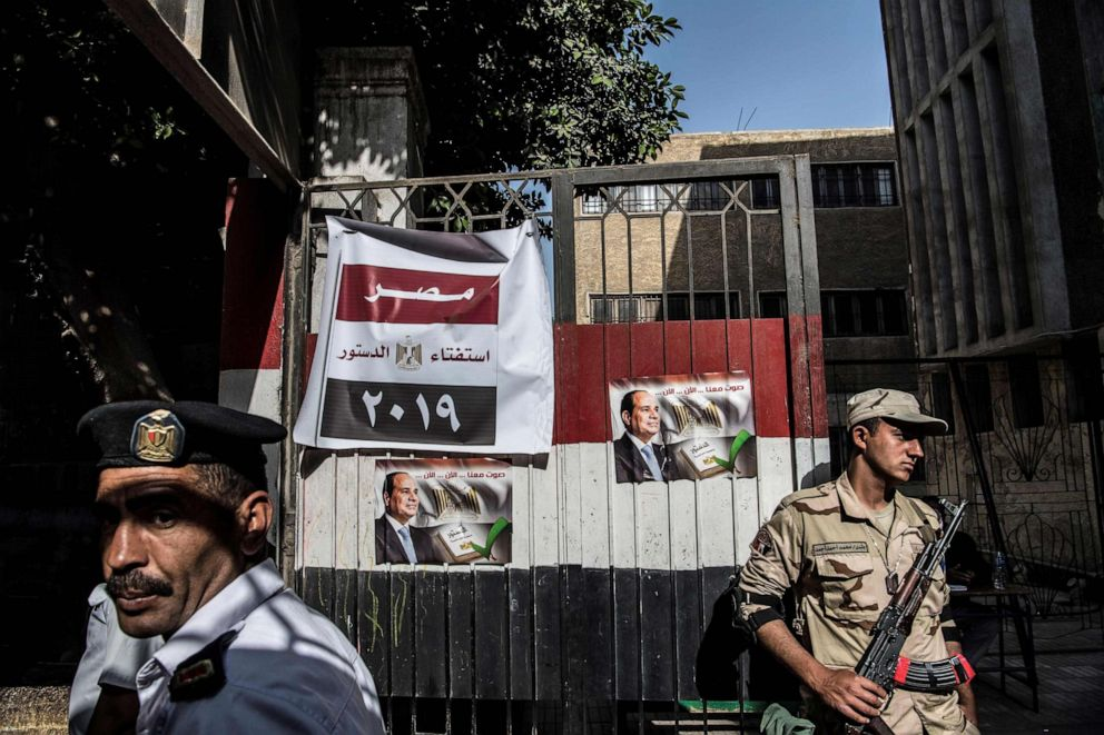 PHOTO: An Egyptian soldier and a policeman stand guard at a polling station during the third day of a referendum on constitutional amendments in Cairo, April 22, 2019.