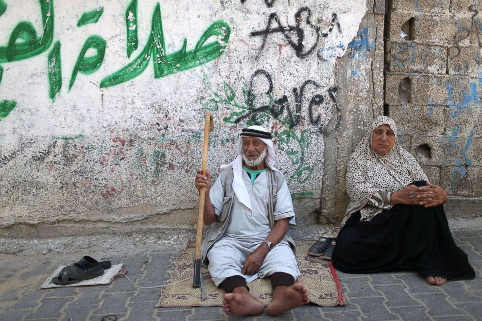 PHOTO: Palestinians sit outside their house at Khan Younis refugee camp in the southern Gaza Strip, June 20, 2018.