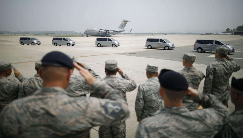 PHOTO: U.S. soldiers salute before vehicles carrying boxes containing remains believed to be of U.S. soldiers who died during the Korean War.