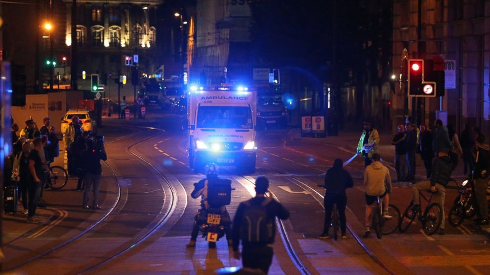People watch an ambulance pass in the street near Manchester Arena after reports of an explosion in Manchester, England, May 23, 2017.