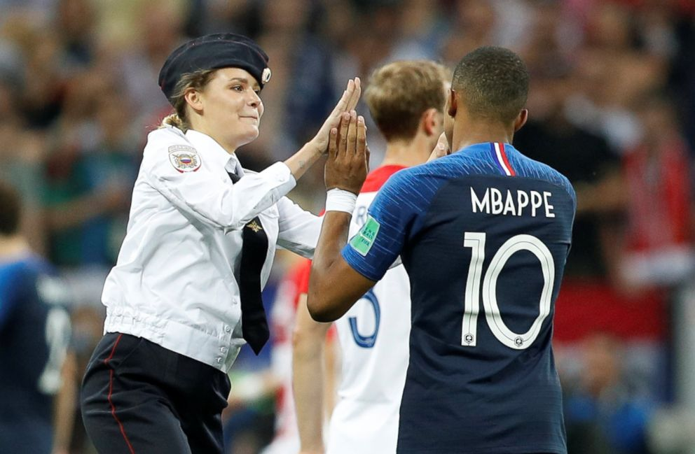 PHOTO: Veronika Nikulshina of Pussy Riot high fives Frances Kylian Mbappe after she staged a pitch invasion during the World Cup final in Moscow, July 15, 2018.