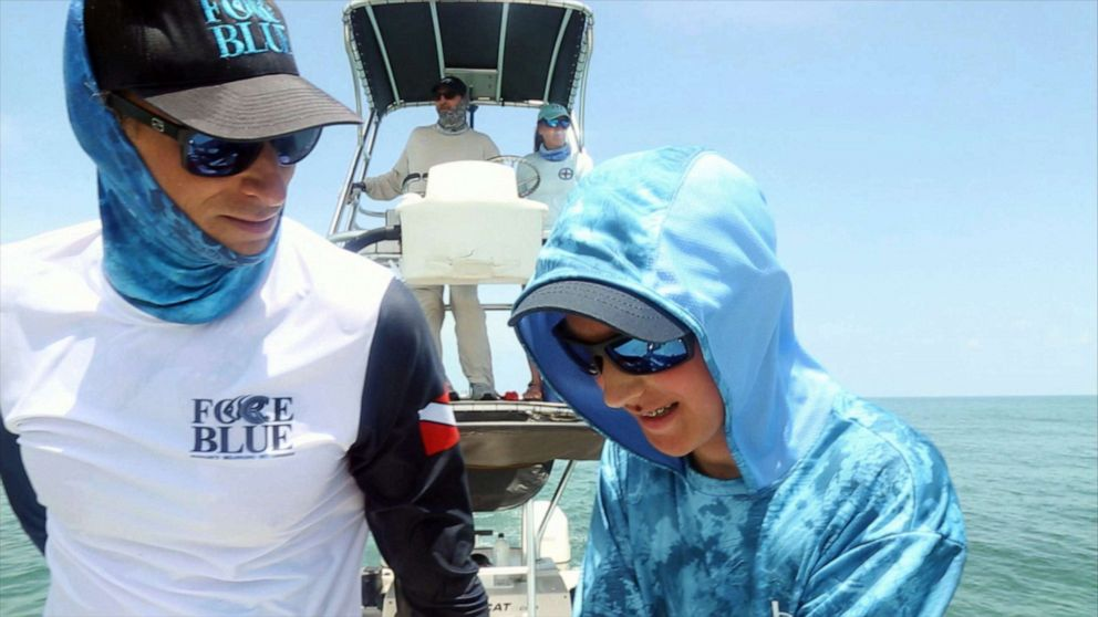 PHOTO: Father and son Force Blue team members Roger, left, and Oz Sparks search for green sea turtles.