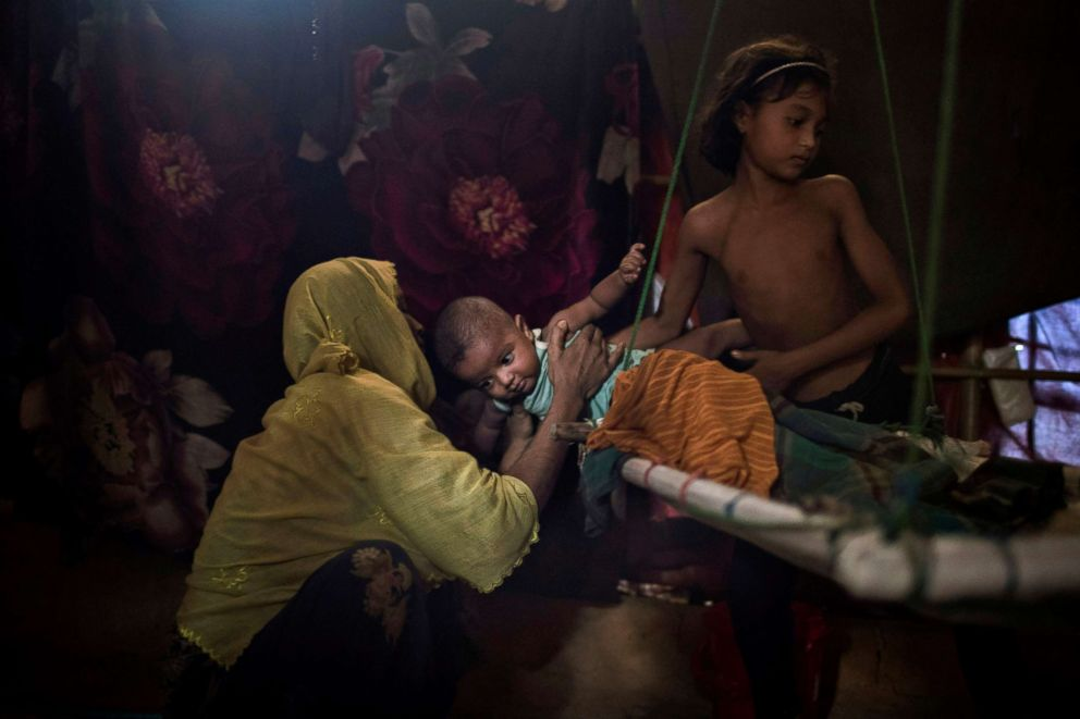 PHOTO: Ms daughter, right, hands over her brother to their mother in their shelter in Kutupalong refugee camp in Bangladesh. M was raped by six soldiers from Myanmars security forces after they strangled her 2-year-old son to death, June 26, 2018.
