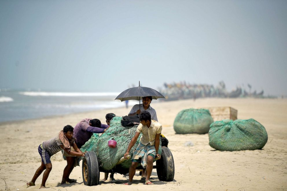 PHOTO: Rohingya refugees push fishing nets along the beach on Shamlapur beach in Coxs Bazaar, Bangladesh, March 22, 2018.