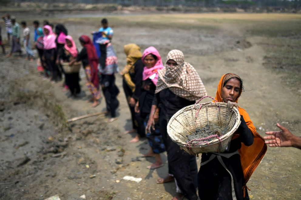 PHOTO: Rohingya refugee women carry baskets of dried out mud from the riverbed to help raise the ground level of the camp in preparation for monsoon season in Shamlapur refugee camp in Coxs Bazaar, Bangladesh, March 24, 2018.