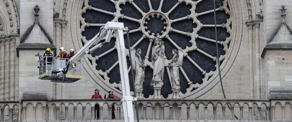 PHOTO: Firefighters outside the south transept Rose window, secure Notre-Dame Cathedral in Paris on April 16, 2019, in the aftermath of a fire that caused its spire to crash to the ground.